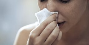 Woman blowing nose and sneezing
